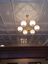"<h5>Historic Original Tin Ceiling</h5><p>The gas-look lights (note the 'key' to ""turn on"" the gas) and the restored original tin ceiling. The walls dividing the the Box Office space are 8' high to allow full visibility of the original 12' high tin ceiling -- creating a more open and roomier fell to the space.</p>"