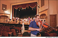 Bernard Di Gregorio tunes his viola before rehearsal in the new Ariel-Ann Carson Dater Performing Arts Centre in Gallipolis